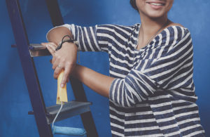 woman holding a paint roller while leaning on a ladder