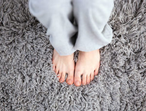 feet standing on a very clean grey carpet