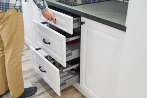 Man opening white kitchen drawers with new handles